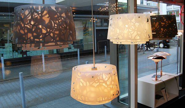 Unser neues Schaufenster mit Leuchten von Louis Poulsen. Links die verspielte Collage-Pendelleuchte von Louise Campbell, rechts unten die limitierte Tischleuchte PH 3½ – 2½ in Kupferoptik und mit Opalschirm. Fotos: Buchholz