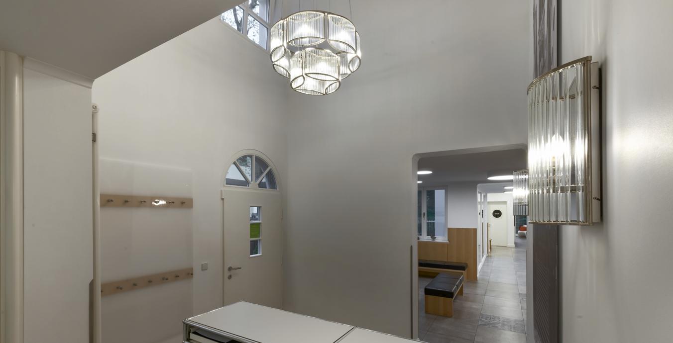 Im Eingangsbereich beeindrucken der Stilio-Kronleuchter und die dazu passenden Wandleuchten.