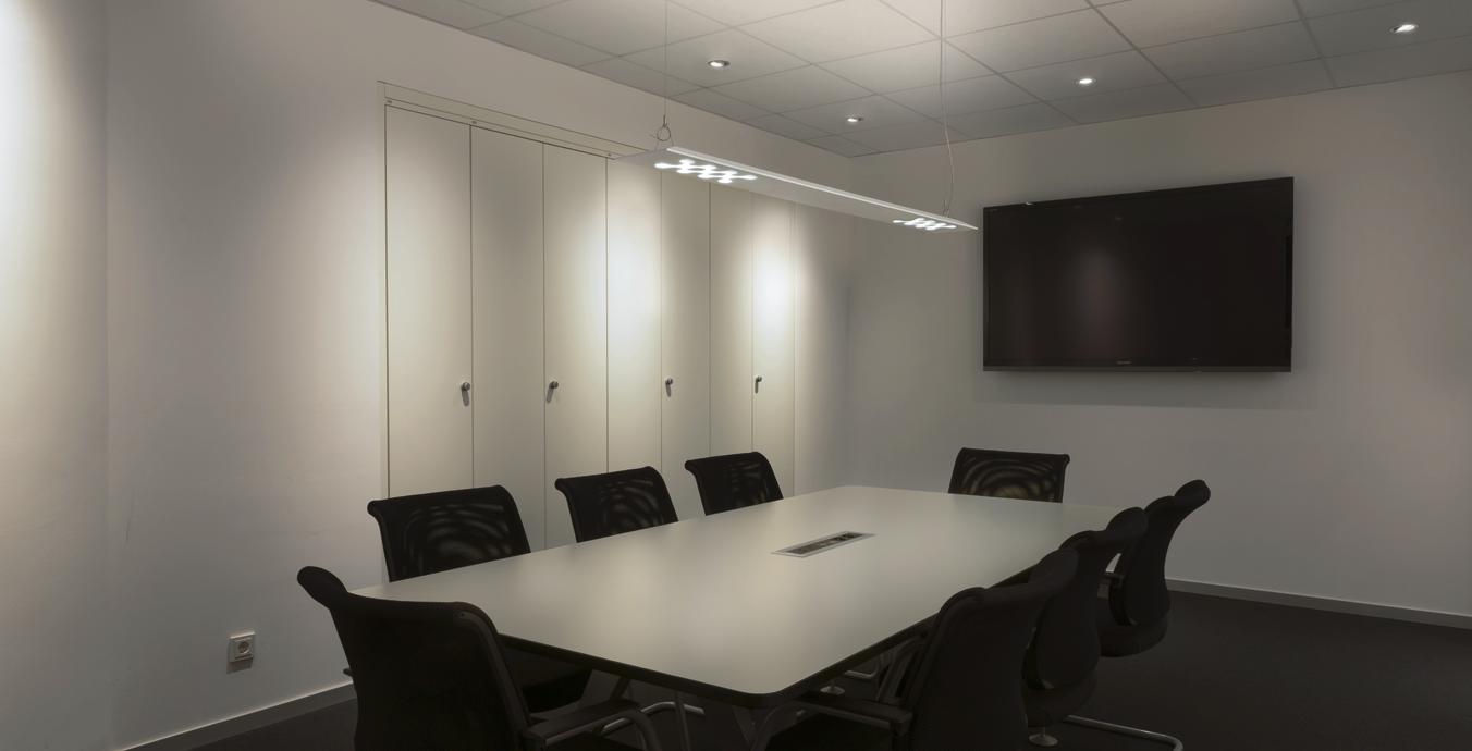 Besprechungsraum mit Trilux-Pendelleuchte und LED-Downlights.