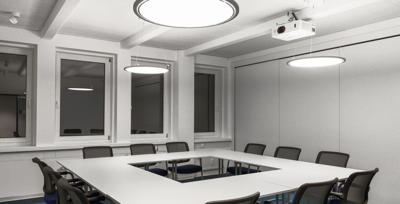 Den Besprechungsraum illuminieren drei runde Lateralo LED-Pendelleuchten von Trilux.