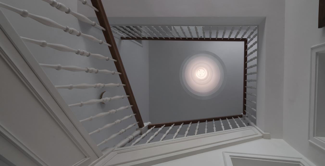 Blick vom Boden an die hohe Decke – nur die Enigma-Pendelleuchte ist eingeschaltet.