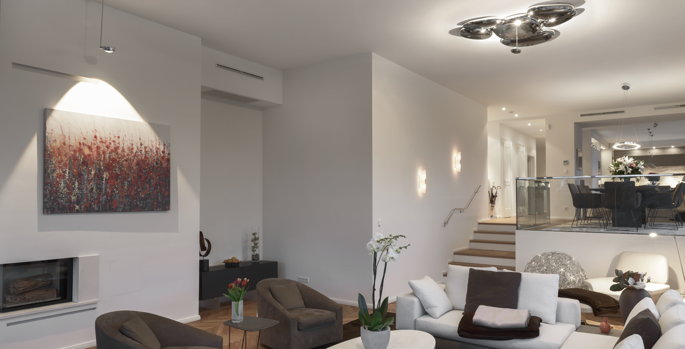 Das Wohnzimmer mit der Skydro Deckenleuchte von Artemide und dem Occhio-Strahler Più alto 3d up.