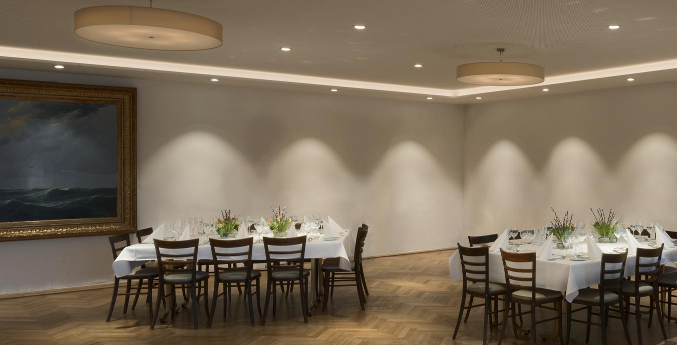 Die beiden großen, deckennah angebrachten Stoff-Leuchten sorgen für dezente Lounge-Atmosphäre.