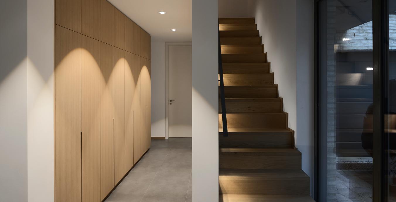 Ein angenehmes Lichtbild im Flur wurde um beleuchtete Treppenstufen ergänzt.
