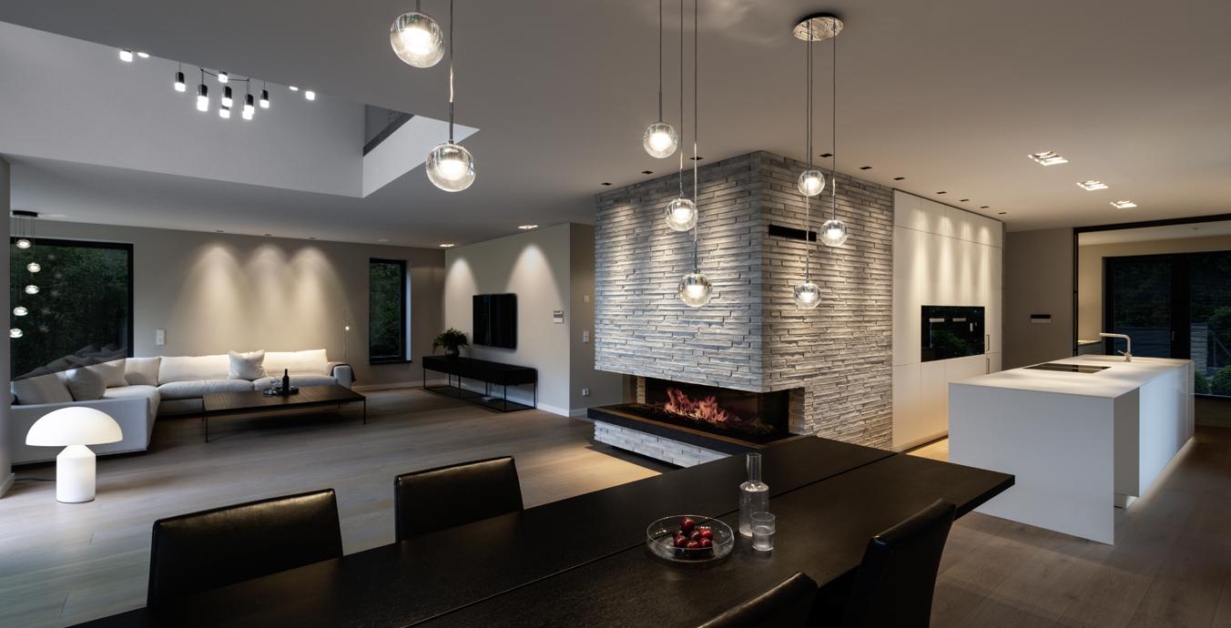 Im Wohn- und Essbereich unterstützt die Beleuchtung die Raumaufteilung.