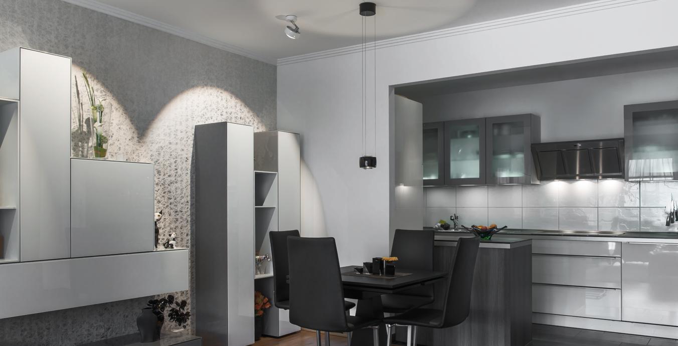 Der gut beleuchtete Esstisch verbindet das Wohnzimmer mit der Küche.