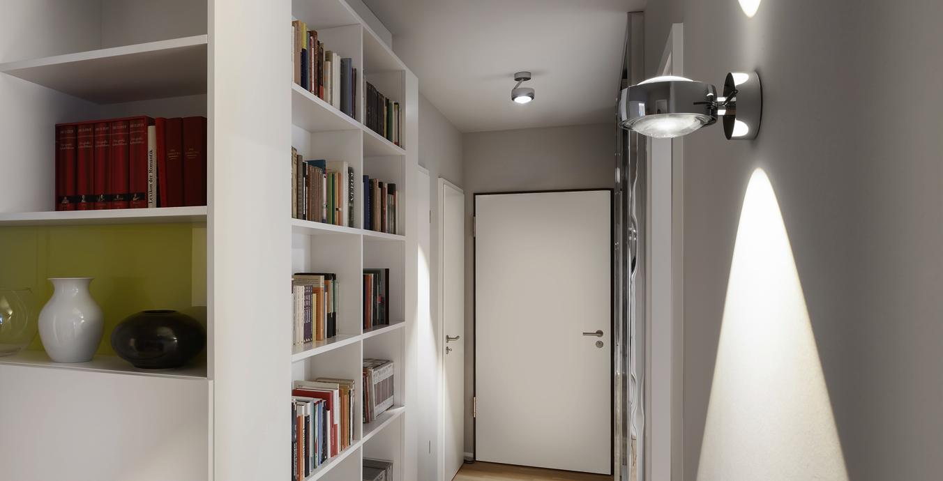Auch im Flur gibt es ein Bücherregal, das allerdings mit Occhio-Leuchten in Szene gesetzt wurde.